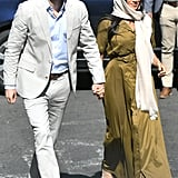 Meghan, Duchess of Sussex Wears An Olive Belted Maxi Dress, Beige Flats, and An Ecru Hair Scarf