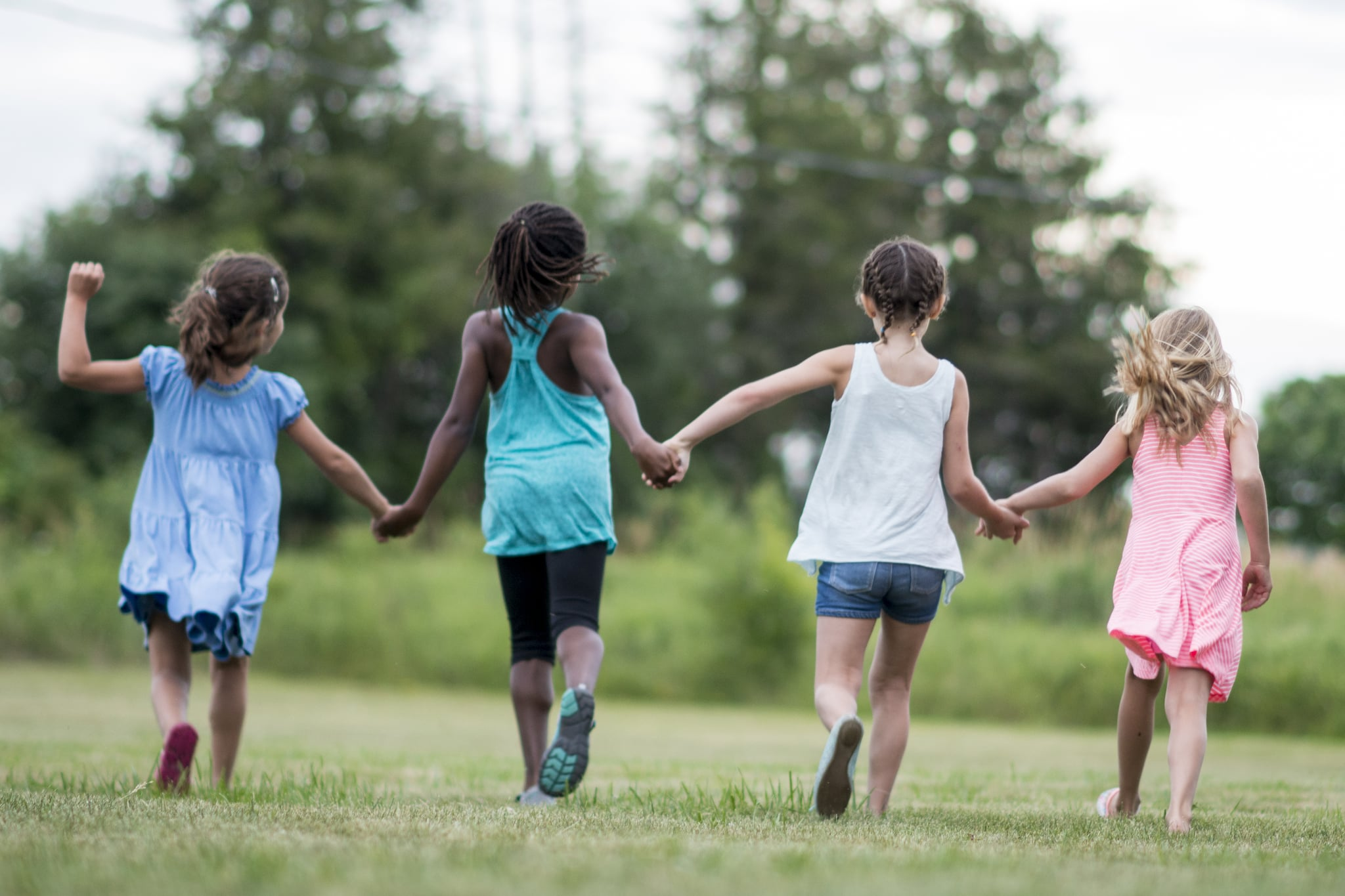 A multi-ethnic group of elementary age children are playing together outside at recess. A group of girls are holding hands and running together in a row.