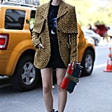 A printed coat, quirky boots, and a colorblocked clutch set this look apart.