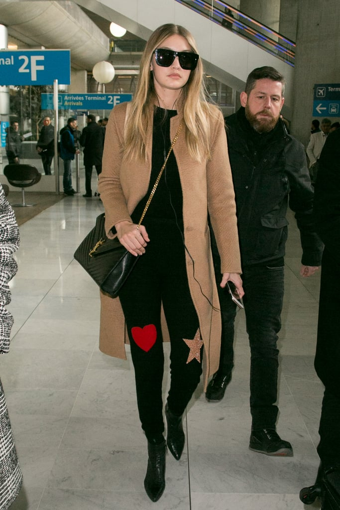 Wearing a pair of black skinnies with patches on them, paired with a black top, camel jacket, and booties.