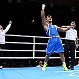 Italy's Clemente Russo put his arm in the air after winning his boxing bout.