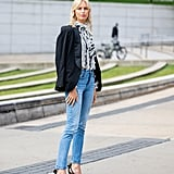Go for an elevated and elegant denim look with a printed silk blouse, blazer, and heels to finish off the outfit.