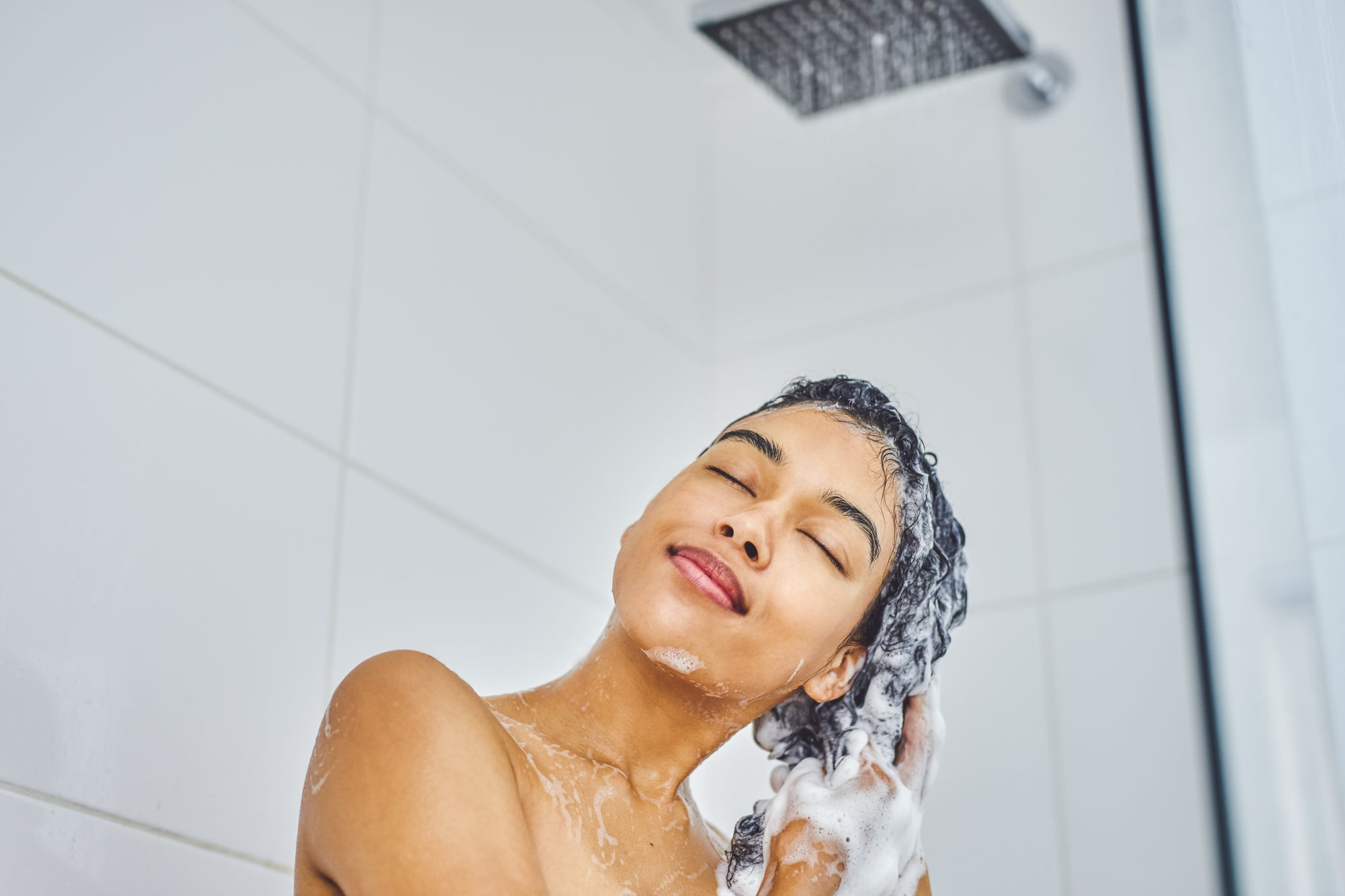 Shot of an attractive young woman washing her hair with shampoo in the shower at home