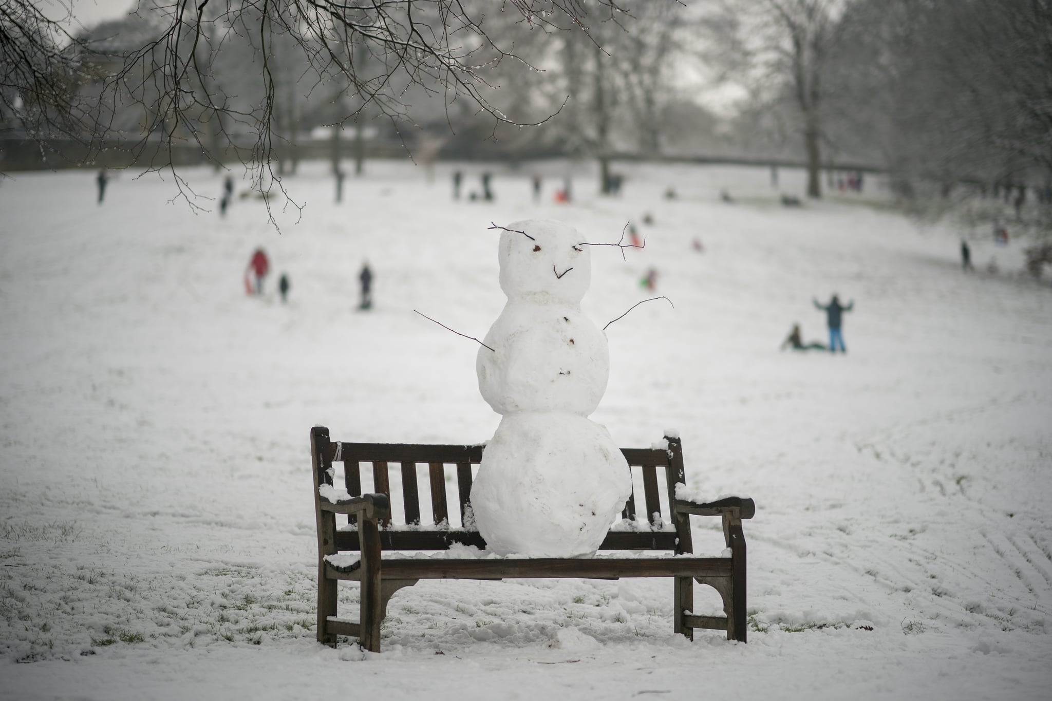 HALIFAX, ENGLAND - DECEMBER 29: A snowman takes in the wintry view from a bench in Shibden Hall Park on December 29, 2017 in Halifax, England.  Travelers are being warned of dangerous roads conditions across the UK, as wintry weather brings snow and ice and an amber warning from the MET Office.(Photo by Christopher Furlong/Getty Images)