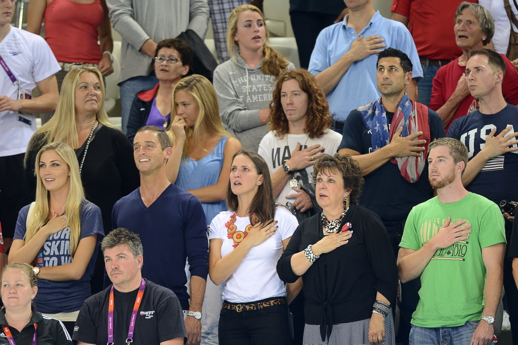Megan Rossee, bottom left, stood for the National Anthem alongside Michael Phelps's family at the Olympics in late July.