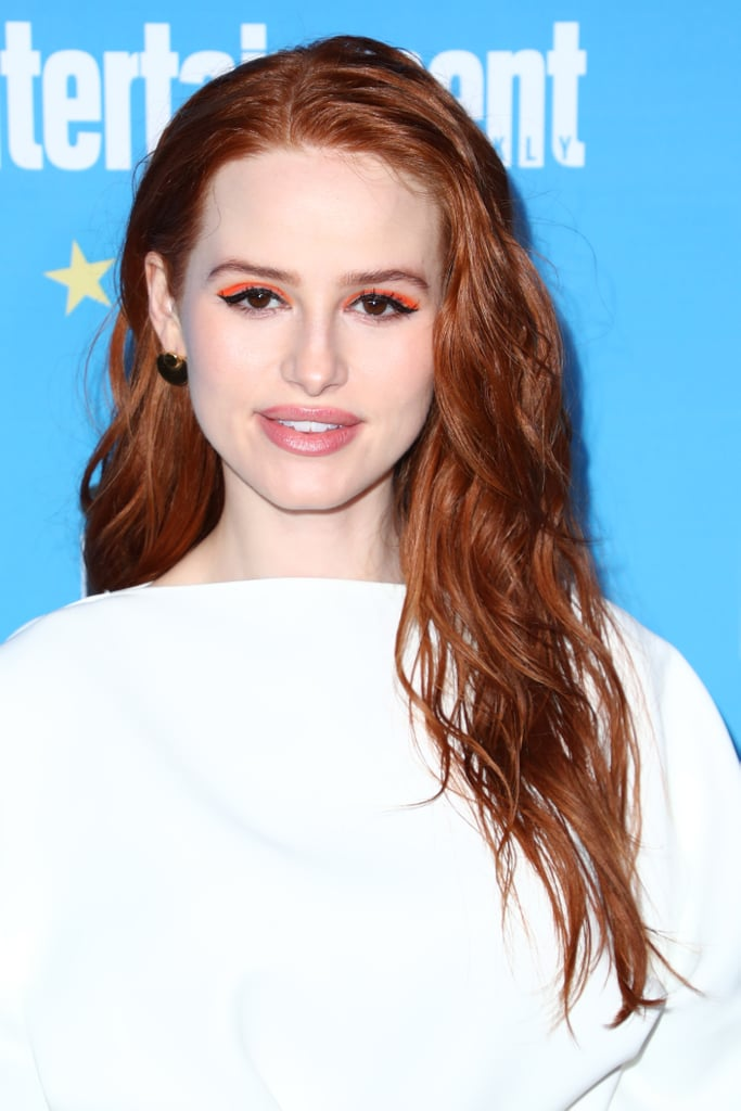 Madelaine Petsch attended the Entertainment Weekly Comic-Con party alongside her Riverdale costars, wearing this Summer's biggest beauty trend on her eyes. The actress, who plays Cheryl Blossom on the hit CW series, wore neon orange across her eyes with a thick black cat eye, which complemented her black and orange skirt. Neon colors have been seen on the eyes on Rowan Blanchard and Becky G, and the same hues have been spotted across the fingertips of Rihanna and Dua Lipa. Billie Eilish has even worn the trend in her hair as well as on her nails, so it's no wonder Petsch decided it was her turn to try the vibrant trend. Check it out ahead.