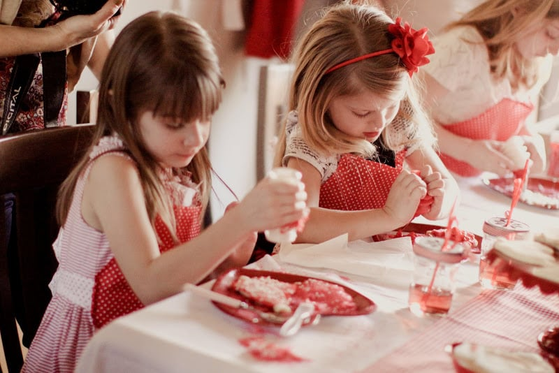 The girls wore red aprons to keep from getting messy during the fun cookie decorating.  Source: Jenny Cookies