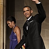 Barack kept a hold of Michelle's hand as he waved to the crowd at an event.