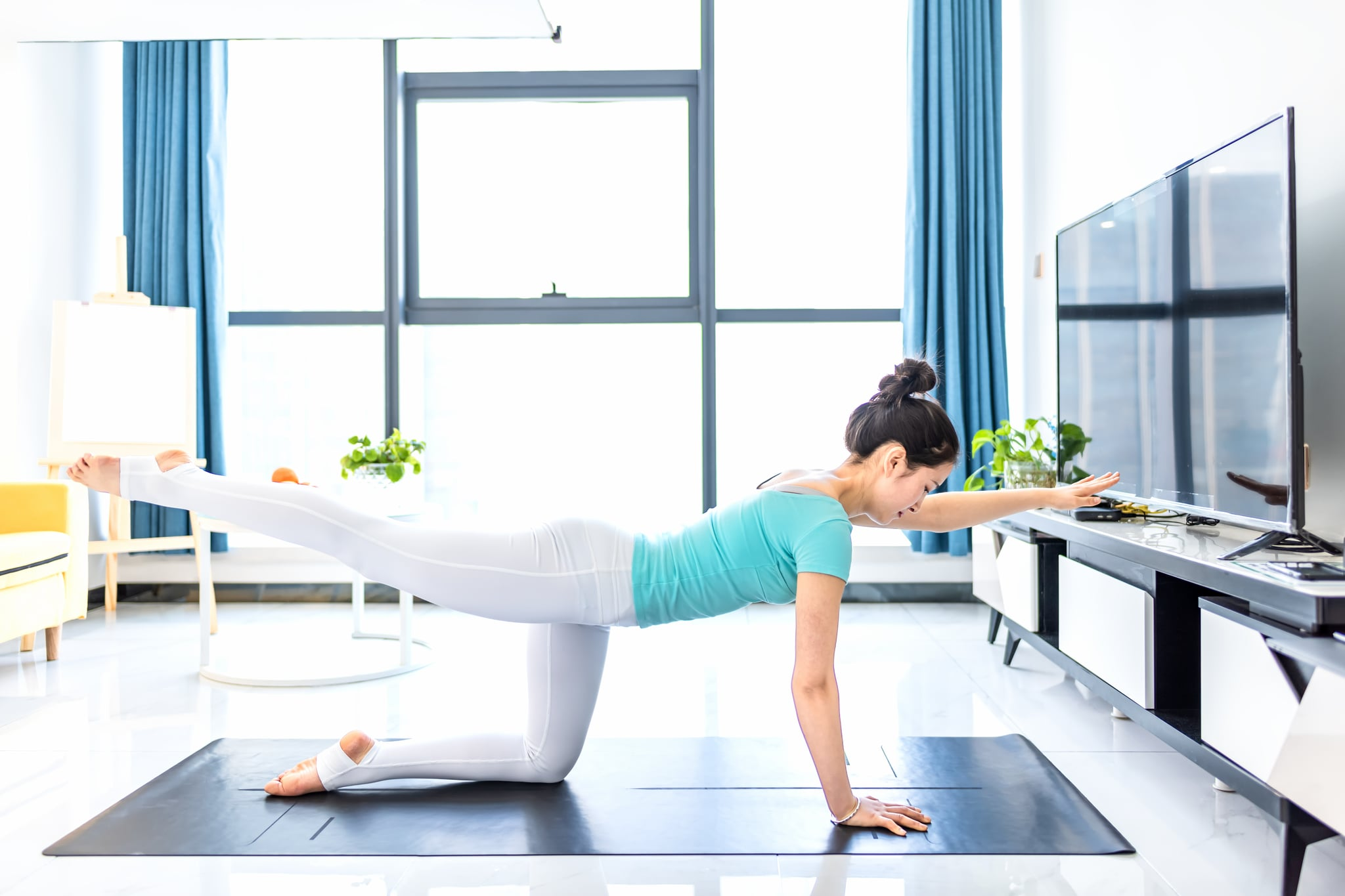 Young asian woman practicing yoga in living room