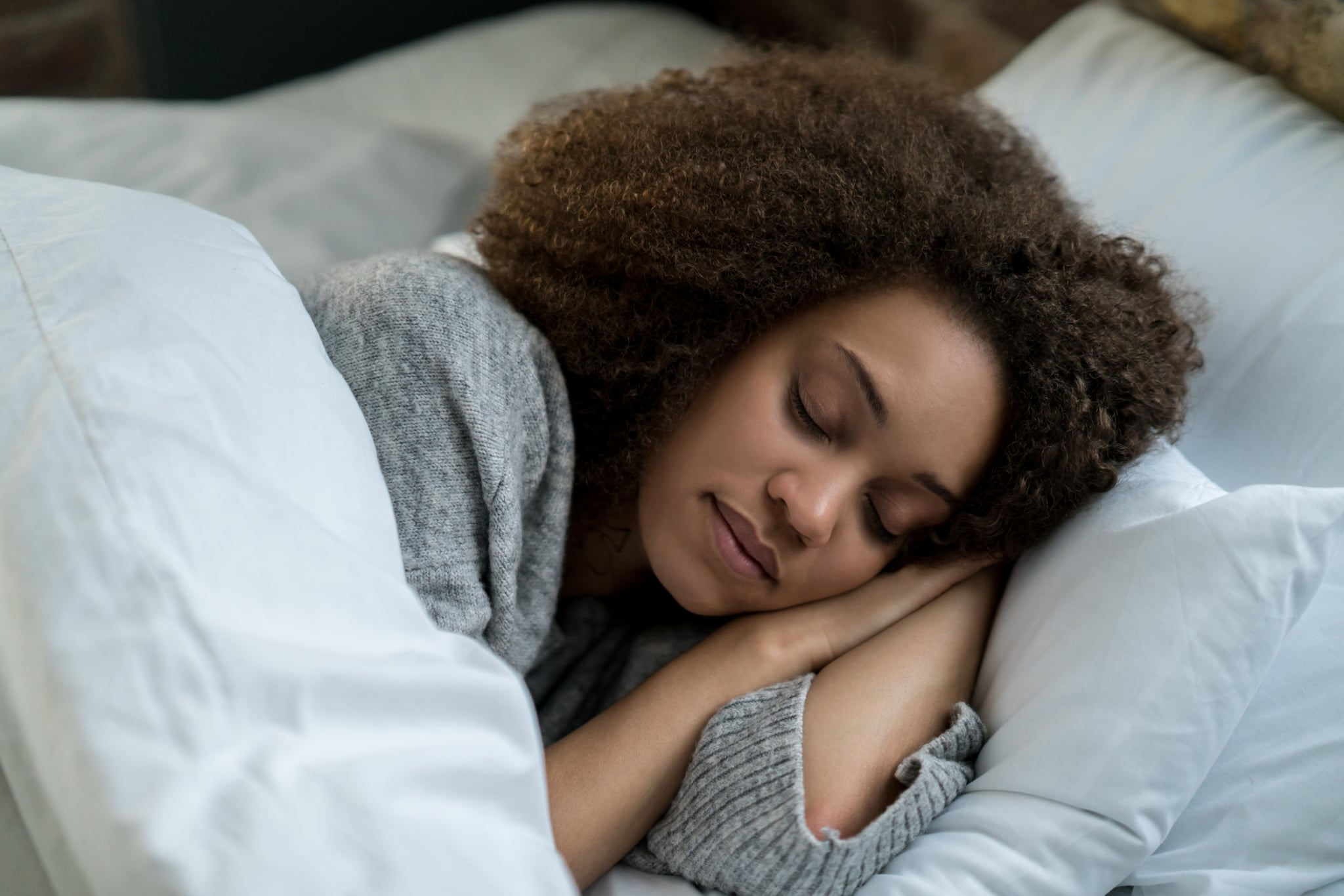 Portrait of a beautiful African American woman sleeping in bed and looking very peaceful - lifestyle concepts