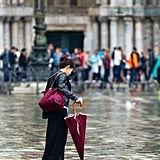 The yearly high tide came to Venice, Italy, leaving one woman to wade her way through the street.