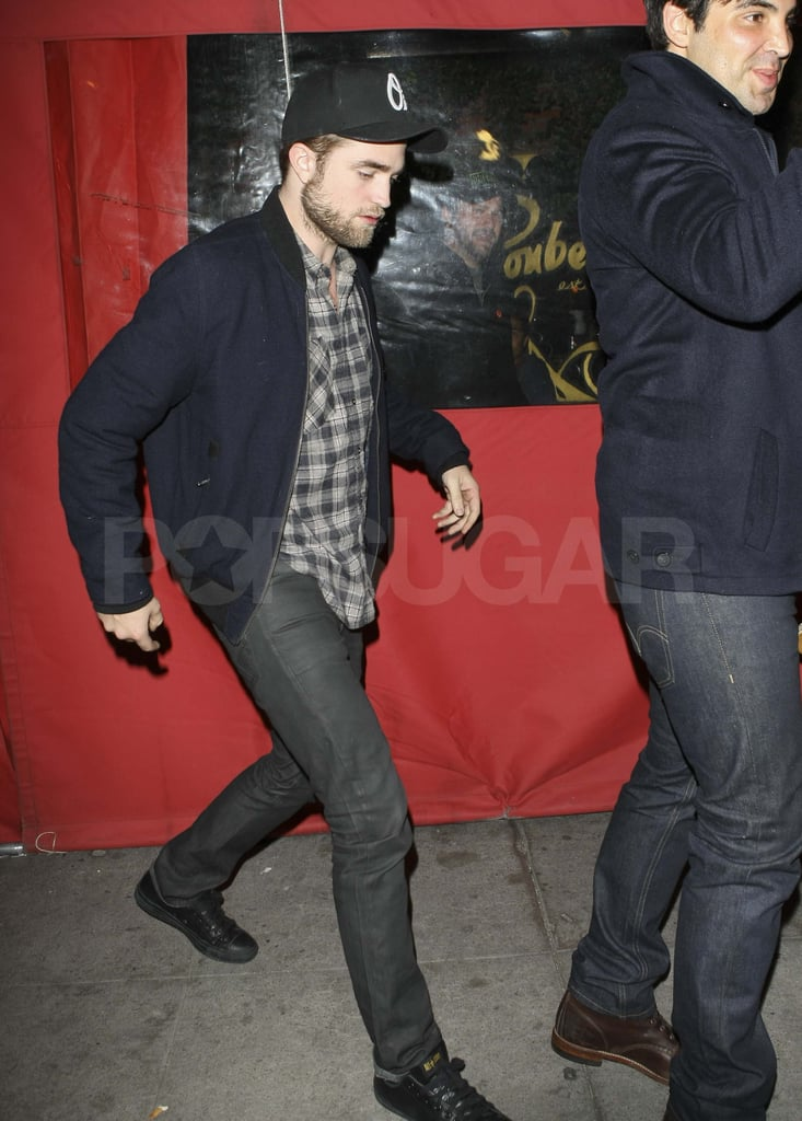Robert Pattinson in a plaid shirt and hat.