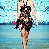 Gigi's first Anna Sui look was so sexy. Her sequined halter neck featured a fringe hemline which extended beyond her rose-embroidered leather minishorts. Gigi walked the runway in complementing red and yellow platforms that she played up with lacy ankle socks.