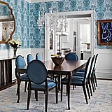 Blue is once again prominent in the dining room thanks to the printed wallpaper and chairs. A piece of bunny art by Hunt Slonem hangs on the wall. The chandelier is from Windfall.