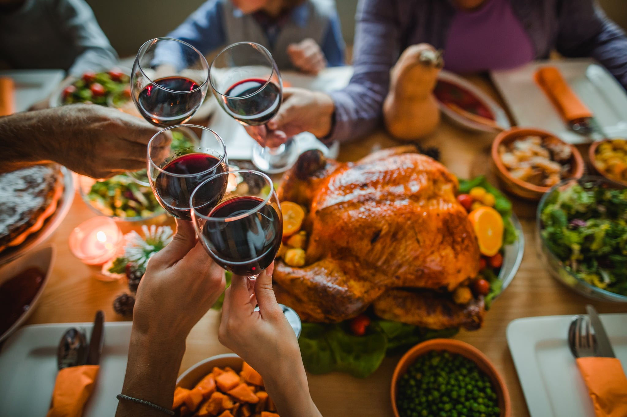 Group of unrecognizable people toasting with wine during Thanksgiving dinner at dining table.