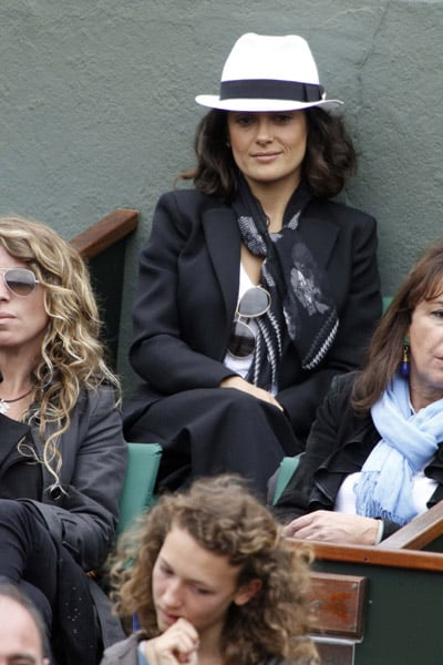 Salma Hayek watched the French Open in a chic menswear-inspired ensembe: black suit, white fedora, silk scarf, aviators.