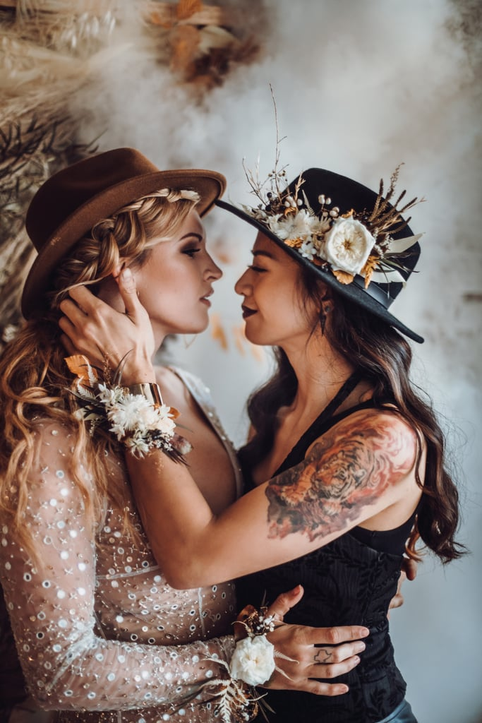 After participating in numerous styled shoots, photographer Aisha Khan finally got the opportunity to produce her own styled shoot last October — and she went all out with this goth-Western themed wedding, inspired by a faux gold longhorn she found. The styled shoot featured two models — one in a chic black tank top and leather pants, and the other in a gorgeous gown with intricate beading and embroidery. The two brides posed in a rustic studio with brick walls and numerous props around them. The room was decorated with oil lamps, ground-based installation pieces with tumbleweeds, and a showstopping jet-black four-tiered cake! Smoke emerged from a fog machine to add to the ambiance of the room. They stuck to a black-and-gold color scheme that added an elegant flair to the wedding theme.  The models then posed alongside a wooden table that was decorated with black flowers, gold cutlery, and long black candles. It gave the room a gothic meets bohemian vibe. Aisha worked really hard with a group of talented vendors to create this spectacular styled wedding. Keep reading to check out the stunning photos!      Related:                                                                                                           A Corgi Ring Bearer, a Polaroid Guest Book, and a Happy Couple! This Autumn Wedding Was Picture Perfect