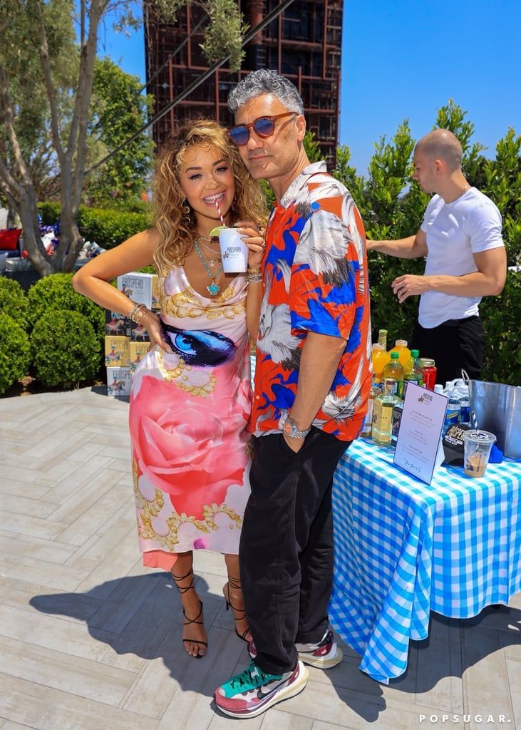 """Rita Ora and Taika Waititi are making things official! After sparking romance rumours back in April, the pair made their first public appearance as a couple at the singer's Fourth of July rooftop party in LA. Rita and Taika rocked matching colourful ensembles and flashed sweet smiles as they posed for pictures together at the star-studded bash, which also brought out Anya Taylor-Joy, Jodie Turner-Smith, Joshua Jackson, and Ashley Benson.  Rumours of a romance between the 30-year-old singer and the 45-year-old director first began swirling in April when Rita posted a photo album on Instagram, which included a snap of Taika with his arms around her. """"Good times, memories, random things on my phone and the ones I love..❤️ #midweekupdate,"""" she casually captioned it. The following month, the two were spotted packing on the PDA at a party with Tessa Thompson, and they've appeared to be going strong ever since."""