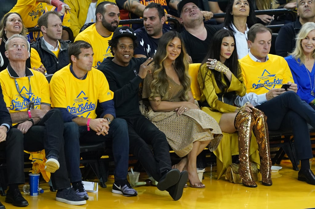 "Beyoncé and JAY-Z were front and centre at game three of the NBA finals in Oakland, CA, on Wednesday. The 37-year-old singer and 49-year-old rapper sat courtside as the hometown Golden State Warriors battled the Toronto Rapters at the Oracle Arena. Naturally, Bey looked fabulous, rocking a neutral ensemble with a longline grommet jacket. Meanwhile, Jay — who recently reached billionaire status — sported an all-black outfit from head to toe. Bey and Jay's appearance also generated some buzz for another reason. In a video posted by ESPN, the dynamic duo were waving at a camera when the clip captured an *ahem* interesting moment between JAY-Z, Beyoncé, and Nicole Lacob — the wife of Warriors owner Joe Lacob. At one point, Nicole is seen leaning over Bey to chat with Jay, and the Beyhive would like to know exactly what was going on. Jay-Z and Beyoncé are courtside for Game 3 😎 pic.twitter.com/6mmJuN8Odn— ESPN (@espn) June 6, 2019    Beyoncé didn't look too thrilled about having her personal space invaded — nor did she look too thrilled that it happened so Nicole could speak to her husband of 11 years. It might not be a coincidence that in the photos of Bey and Jay, the singer has her body positioned toward her beau rather than directly forward like how she was sitting at the Houston Rockets game weeks ago. It also doesn't help that Nicole herself posted a photo of her touching Beyoncé's hair (a major no-no), and the singer looks pretty uncomfortable. Now, I don't want to jump to conclusions based off a 13-second clip. I wouldn't expect Beyoncé to keep a smile the whole time, because they showed up to attend a game, not to constantly look pleasant on camera. Some people are even speculating that Nicole is simply taking Jay's drink order as it appears as though she's mouthing the words, ""With lime?"" Not to mention, Bey and Nicole are seen laughing together in some pictures, which suggests they were both totally fine. However, I would like to know if Nicole at least pardoned herself before leaning that close into Beyoncé to speak over her. I'm sure it's loud and rowdy in there (it is the Oracle Arena, after all), but a quick ""sorry"" or ""excuse me"" before or after the interaction with Jay would have gone a long way. Maybe I just stan too hard for . . . manners? Maybe Nicole did excuse herself off camera? Who knows. At any rate, Beyoncé is the capital B, and ""she don't need no hype."" And the capital B means she's 'bout that life. Translation: Queen Bey can hold her own, and she did.      Related:                                                                                                           We Made a Family Scrapbook For Beyoncé, Jay Z, and Blue Ivy, Because Why Not"