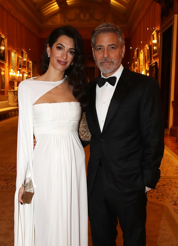 """It's date night for George and Amal Clooney! On Tuesday, the couple stepped out for a special dinner celebrating The Prince's Trust at Buckingham Palace. The event was hosted by Prince Charles and brought out a handful of stars including Benedict Cumberbatch, Chiwetel Ejiofor, Luke Evans, Tamsin Egerton, and Josh Hartnett. George cut a suave figure in a black tux, while Amal was a vision in white — if we didn't know any better, we'd say these two were getting married. In addition to supporting Charles's youth charity, George and Amal are quite close with the royal family. Not only were they both front and centre at Prince Harry and Meghan Markle's wedding last May, but Amal attended Meghan's baby shower in NYC last month and George recently came to the duchess's defence following months of scrutiny from the press.  In an interview with Australia's Who magazine, George demanded respect for Meghan, who's been """"pursued and vilified."""" """"She's a woman who is seven months pregnant and she has been pursued and vilified and chased in the same way that Diana was and it's history repeating itself. We've seen how that ends,"""" he added. Sadly, it doesn't look like Meghan and Harry were in attendance, but at least we have these beautiful photos of George and Amal to hold us over until their next appearance.       Related:                                                                                                           George Clooney Demands Respect For Meghan Markle: She's """"Been Pursued and Vilified"""""""