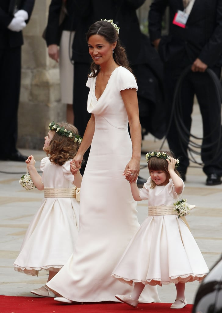 Pippa Middleton arrived at Westminster Abbey wearing a custom ivory gown by Sarah Burton at Alexander McQueen this morning. The crepe cowl front dress had the same button detail and lace trim as the bride's gorgeous McQueen wedding gown. Pippa wore floral diamond earrings and a coordinating headpiece that were made for her by the same jeweller, Robinson Pelham, who designed Kate's earrings. She tended to the young bridesmaids before assisting Kate with her 9 foot train as she entered the church.