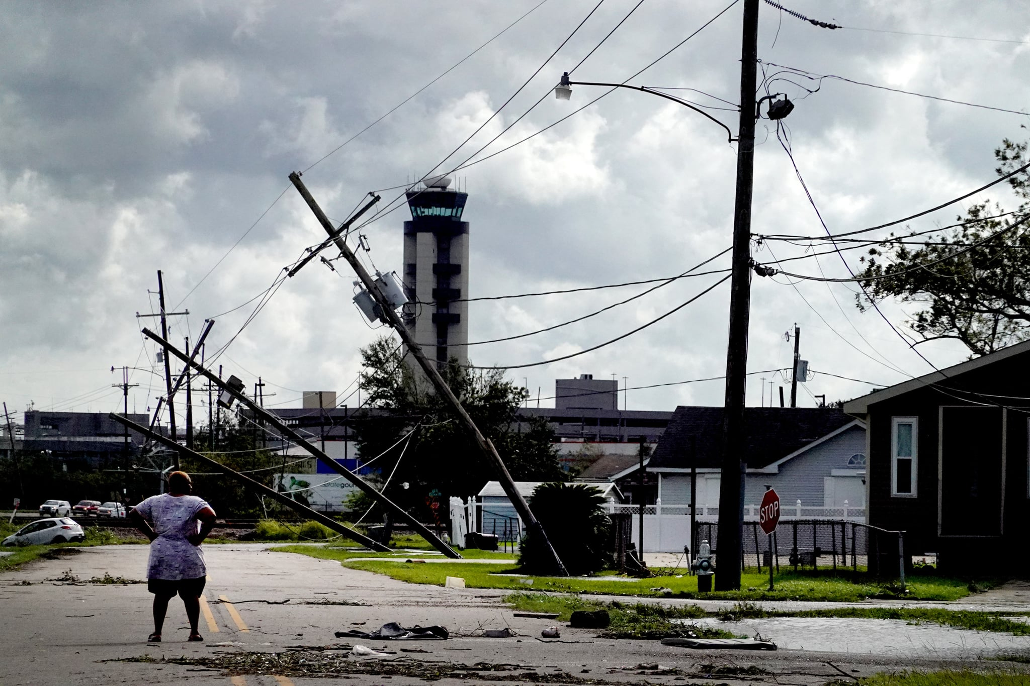 KENNER, LOUISIANA - AUGUST 30: A woman looks over damage to a neighborhood caused by Hurricane Ida on August 30, 2021 in Kenner, Louisiana. Ida made landfall yesterday as a category 4 storm southwest of New Orleans.  (Photo by Scott Olson/Getty Images)