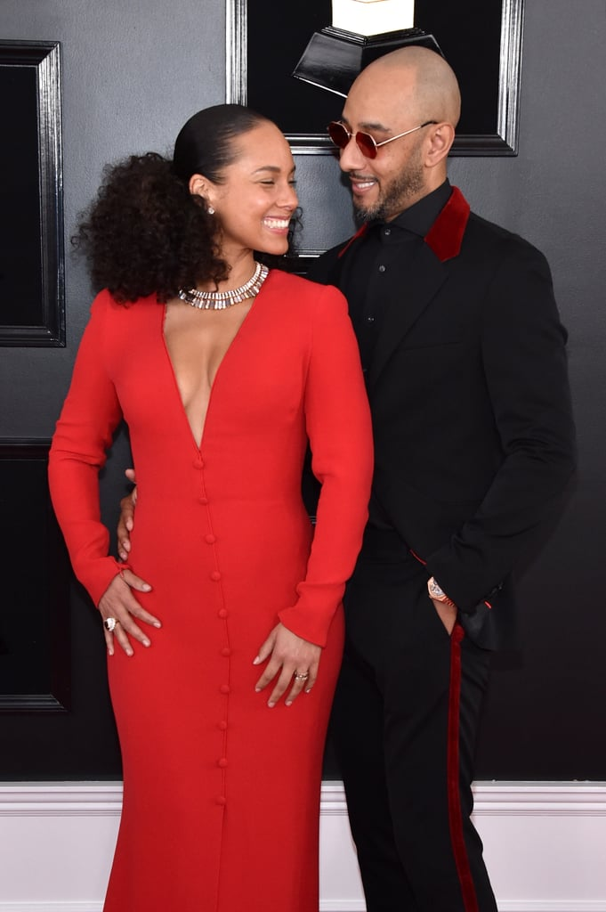 "Alicia Keys's night at the 61st annual Grammys kicked off on a major high note. The 38-year-old singer and musician showed up to the red carpet looking fresh-faced and fiery in a bright, low-cut red gown complete with a silver necklace. She was accompanied by her husband of eight years, producer Swizz Beatz. The two posed on the red carpet together and even gave each other a cute smooch as cameras flashed.  Alicia — who has an impressive Grammys track record — took on the task of hosting the show and definitely brought the energy. In the days leading up to the Grammys, she prepared for her big night with talk show host James Corden when they performed a remix to Lady Gaga and Bradley Cooper's nominated song ""Shallow."" And it seemed to help her get into the zone. She started the show by bringing a majorly powerful female squad on stage: Lady Gaga, Jada Pinkett Smith, Jennifer Lopez, and Michelle Obama! Later on, she wowed the crowd with a performance of her own in which she sang and played not one, but two pianos (casual).  View photos of her big night ahead!      Related:                                                                                                           Lady Gaga, Drake, Cardi B, and Everyone Else Who Won a Grammy This Year"