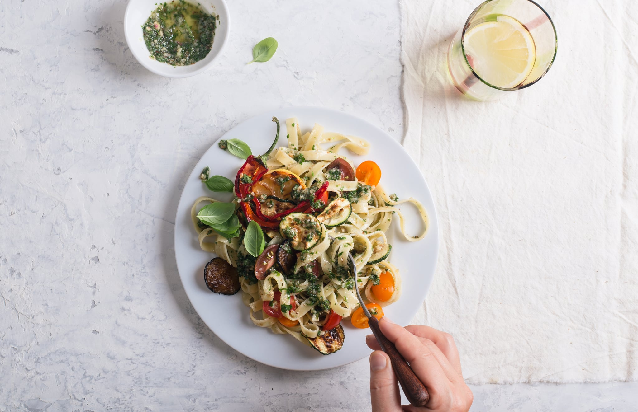 Eating Fettucine with roasted summer colorful vegetables and parsley walnut pesto, delicious vegan meal served with  fresh lemon water on rural table, top view