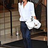 Wearing a white button-down shirt, dark jeans, and sandals.