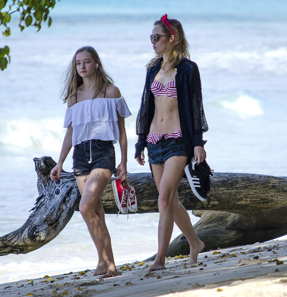 Suki's little sister, Immy, contrasted her high-waisted distressed shorts with a feminine off-the-shoulder top. She held onto a pair of red low-top Converse.