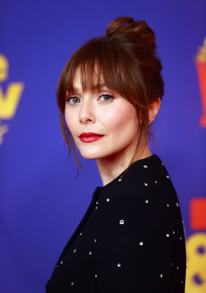 Elizabeth Olsen's Curtain Bangs and Top Knot Hairstyle and Bold Red Lip at the MTV Awards