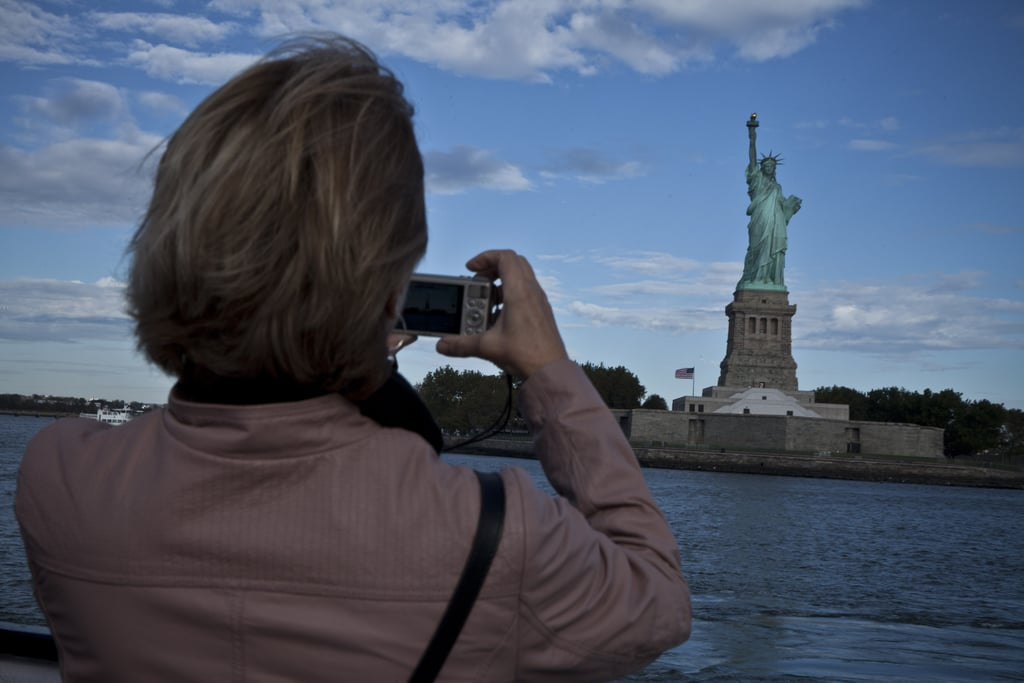 A woman took a picture of the Statue of Liberty on day 12 of the shutdown, the day before it was reopened thanks to funding from New York State.