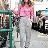A pop of pink on her knit — and a pale pinky hue on her booties — gives these slouchy trousers a girlie contrast.
