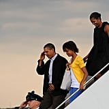 Michelle in a black tunic dress with bows returning from Martha's Vineyard.
