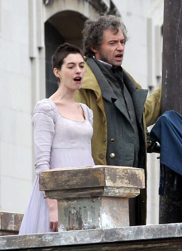 Anne Hathaway was in character as Fantine as she shot Les Misérables with Hugh Jackman in London yesterday. The pair are teaming up on the big-screen adaptation of the Broadway hit, which required them both to undergo physical transformations. Anne cut her hair into a choppy pixie cut, while Hugh has previously been seen sporting a bushy beard and a buzz cut as Jean Valjean on the set. Yesterday, however, he had a head full of gray-tinged curls as he and Anne sang from the rooftops. Between takes, Anne bundled up in a parka and shared a few laughs with her costar. Les Misérables boasts several boldfaced names, including Hugh, Anne, and Sacha Baron-Cohen, but it was stage actress and Hollywood newcomer Samantha Banks who landed the role of Epione. The part was a hotly contested one, with Taylor Swift and Lea Michele both said to be in the running during the casting process.