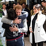 . . . and Prince Harry has become quite the hugger, here seen embracing an athlete at a reception in Australia.