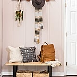 Rustic furniture, like a DIY coat hanger and mod wooden bench ($175-$251) covered in soft pillows ($60) make the space both homey and welcoming.