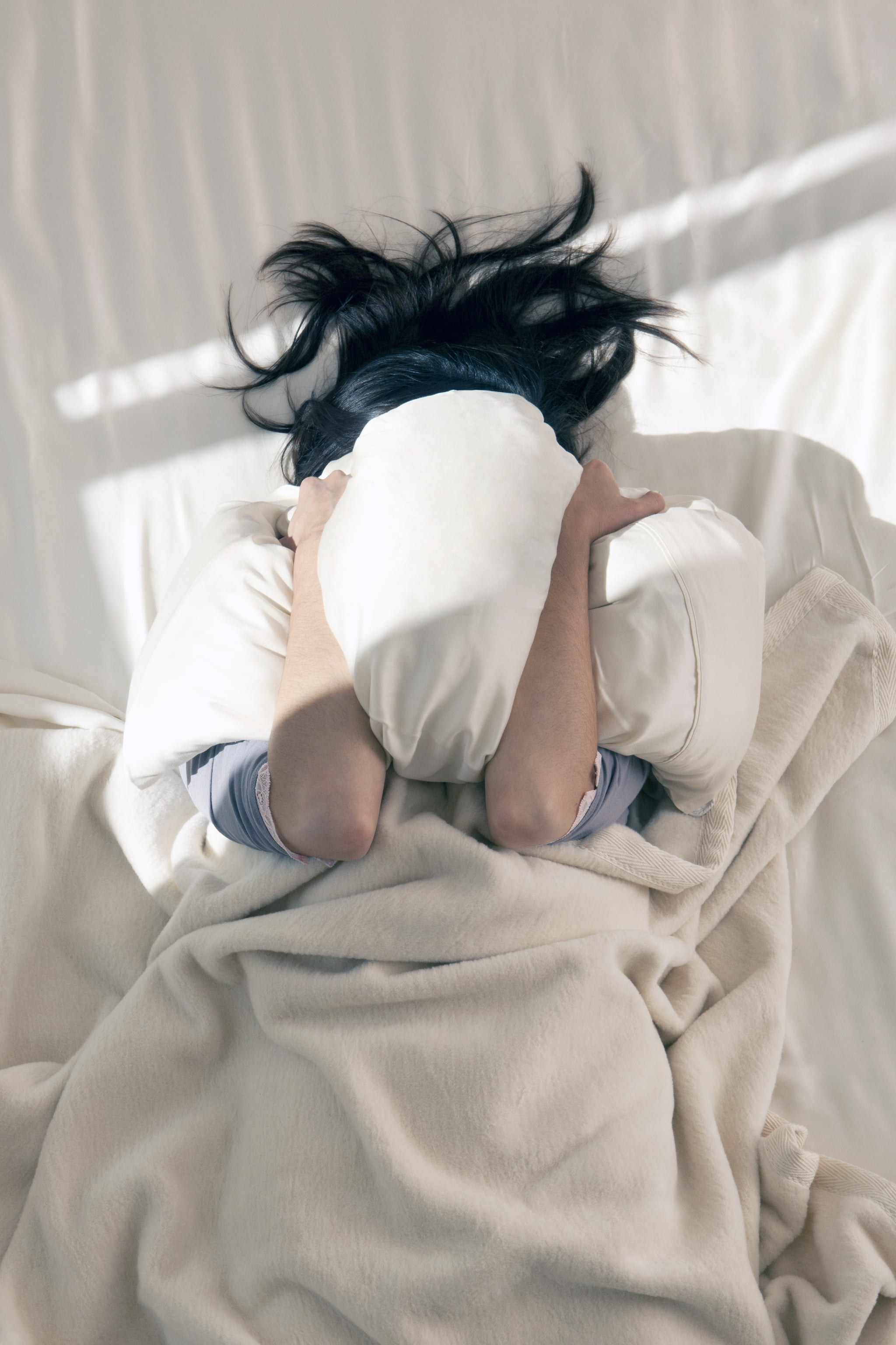 Woman covering her face with pillow beam of sunlight streams in her bedroom