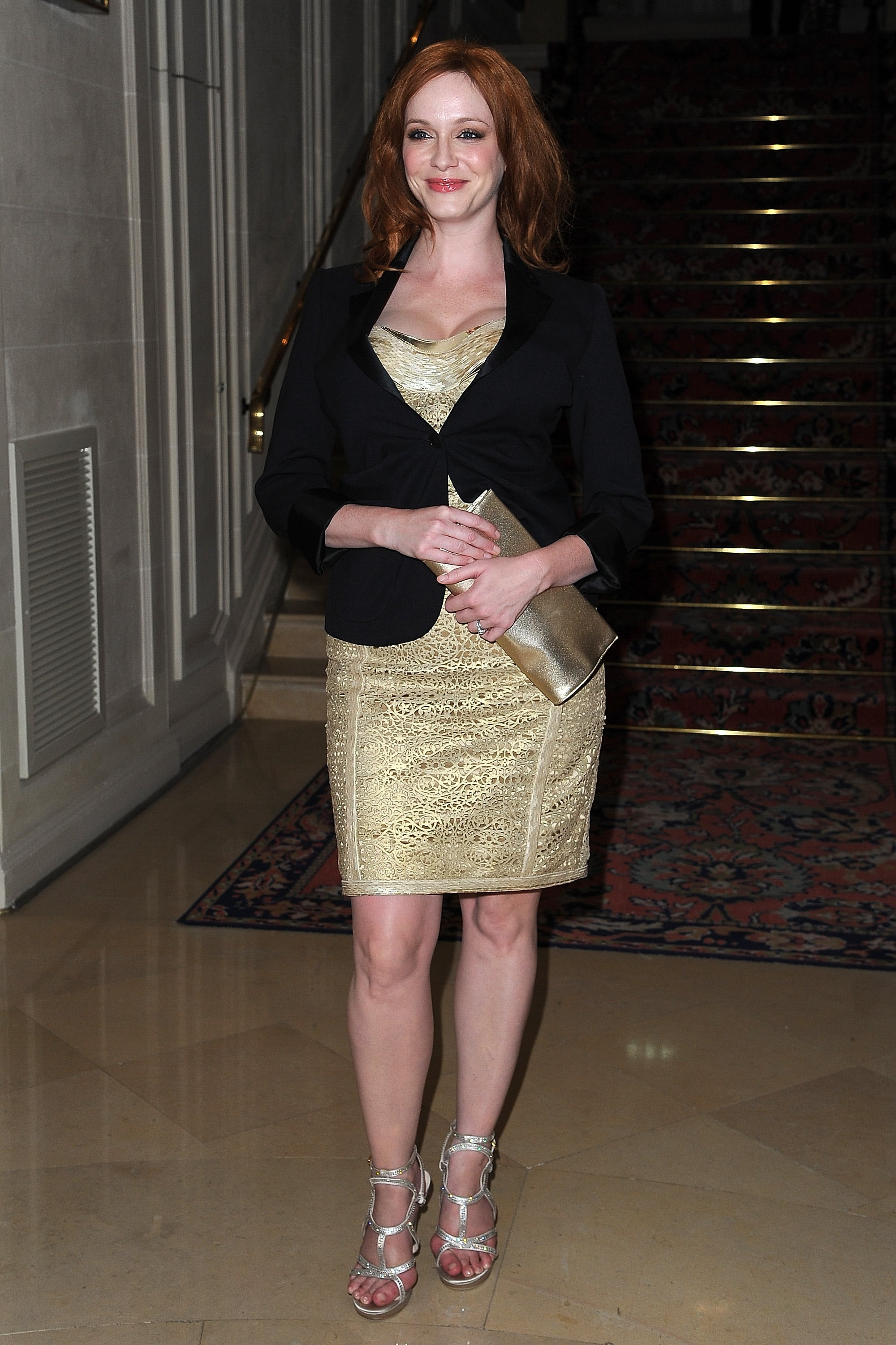 Christina Hendricks wore a gold dress to the Versace show for Paris Fashion Week.