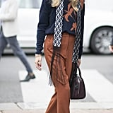 Hack: Meet your long pants with the perfect matching sweater, then wrap an unexpected printed scarf with tassels around your neck and grab your most luxurious satchel.