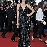 Karolína Kurková channeled her inner mermaid in a sexy, formfitting black halter dress, complete with a shiny, embellished scalelike finish on the Killing Them Softly Cannes red carpet.