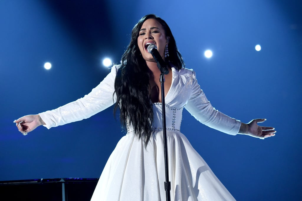 """She's back! Demi Lovato likely left no dry eyes in the house when she made a triumphant return to the Grammys on Sunday night. The 27-year-old delivered a very raw and emotional performance of her new single, """"Anyone,"""" which she wrote and recorded just days before her drug overdose in 2018. Dressed in a white gown, Lovato fought back tears as she belted out the personal lyrics on stage.  In an interview with Zane Lowe, Lovato recently expressed how much the song means to her, saying, """"At the time when I was recording it, I almost listened back and hear these lyrics as a cry for help. And you kind of listen back to it and you kind of think, how did nobody listen to this song and think, 'Let's help this girl.' You know what I'm saying? . . . I was singing this song and I didn't even realize that the lyrics were so heavy and emotional until after the fact."""" Lovato has been hard at work on her upcoming album. While details are still pretty scarce, the singer previously teased on Instagram that she's got """"f**king FIRE coming soon!!!"""" She also teased a second single in her interview with Lowe. """"With the next song that I have coming out, I think I tell more of the story,"""" she said. """"With this one ['Anyone'], it just kind of tells you a little bit about where I was right before and right afterwards."""" On top of new music, Lovato will be singing the national anthem at this year's Super Bowl. Watch Lovato's tear-jerking performance below."""