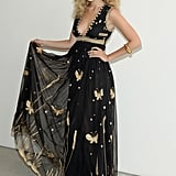 Gigi lifted the train of her dress and posed for a photo backstage, flaunting the design's golden embroidery.