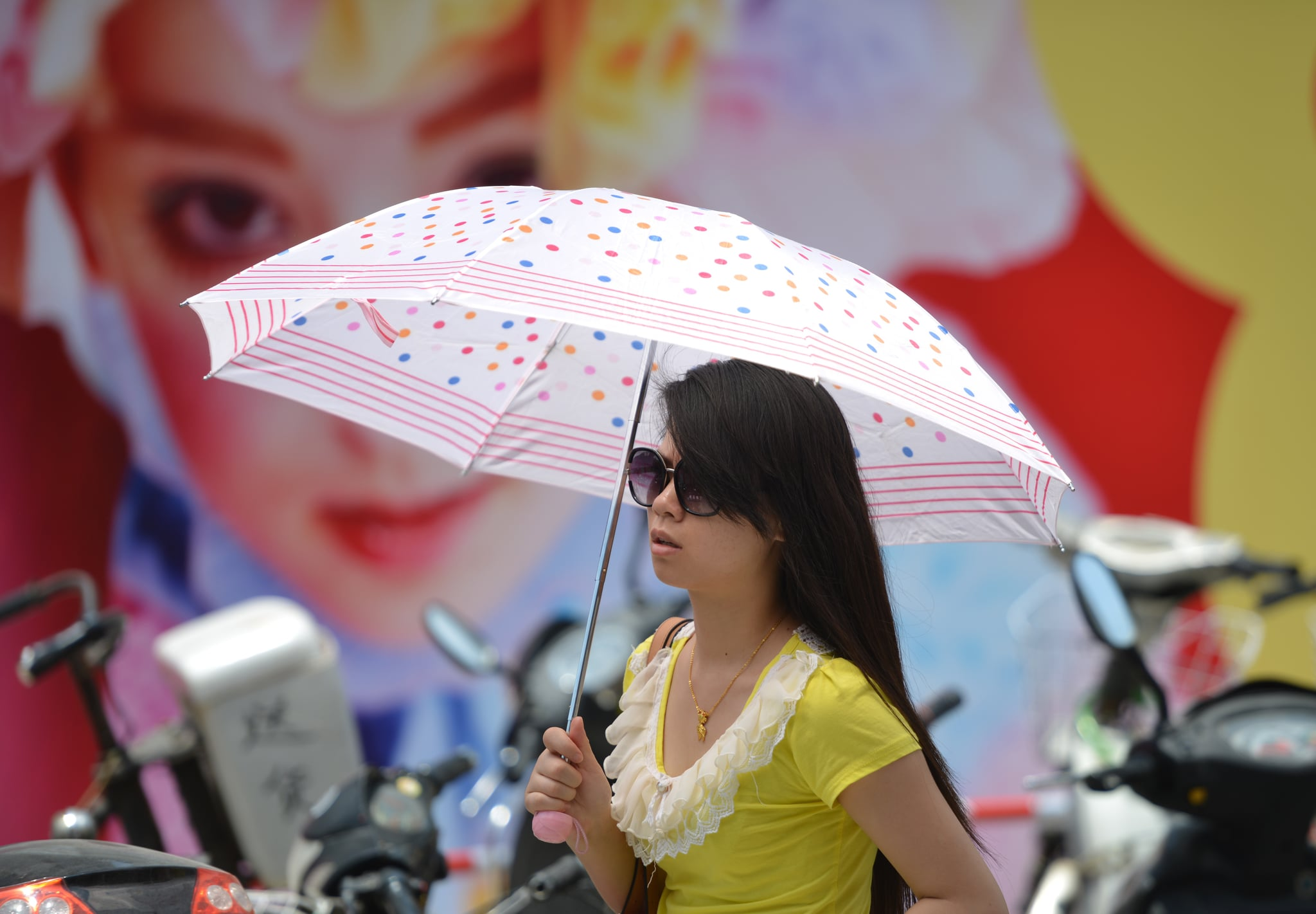 In Shanghai, a woman escaped the sun with the help of a parasol.