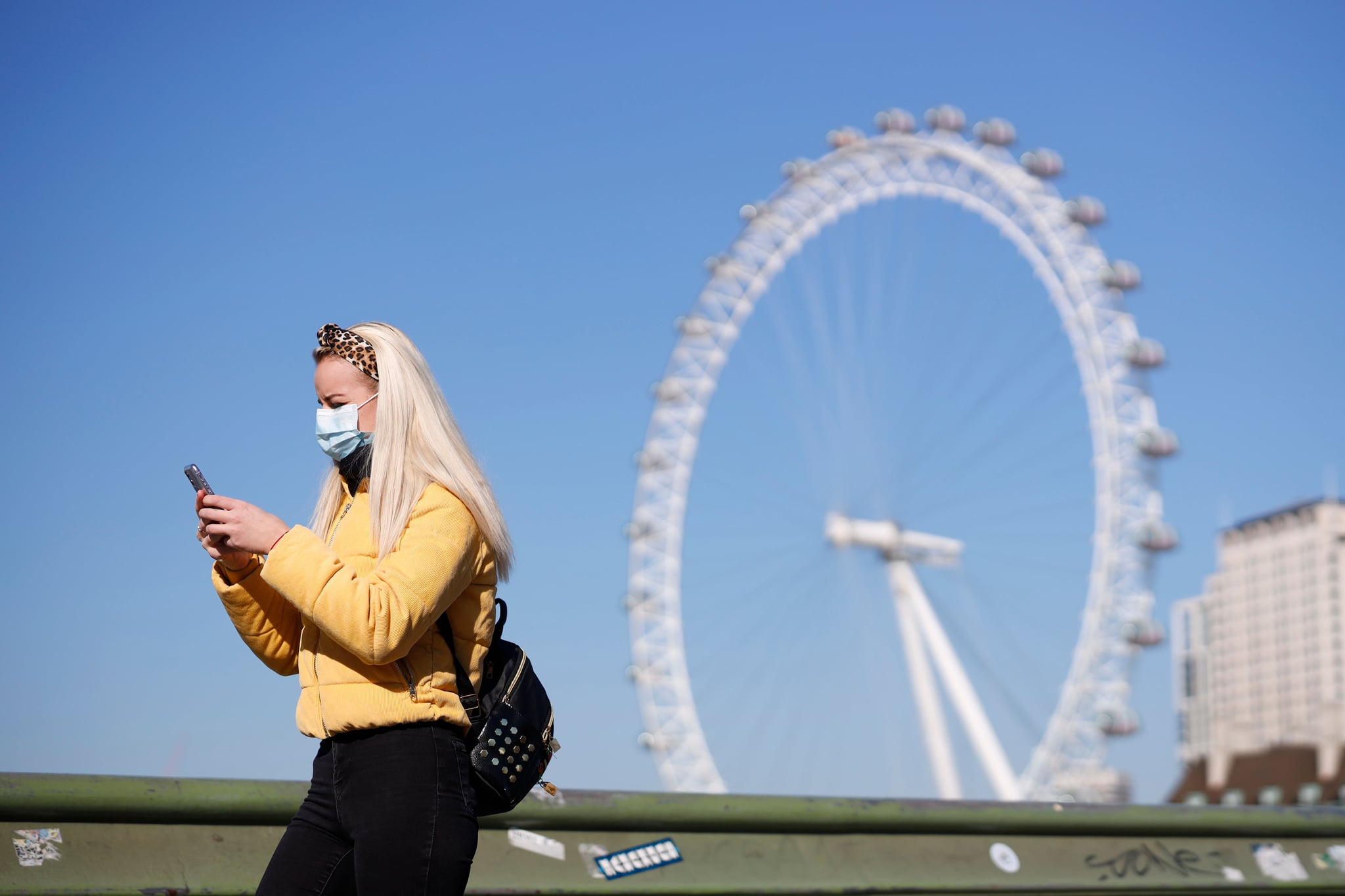 A pedestrian in a mask walks along Westminster Bridge with the London Eye in the backgroud, in a quiet central London on March 25, 2020, after Britain's government ordered a lockdown to slow the spread of the novel coronavirus. - Britain was under lockdown, its population joining around 1.7 billion people around the globe ordered to stay indoors to curb the