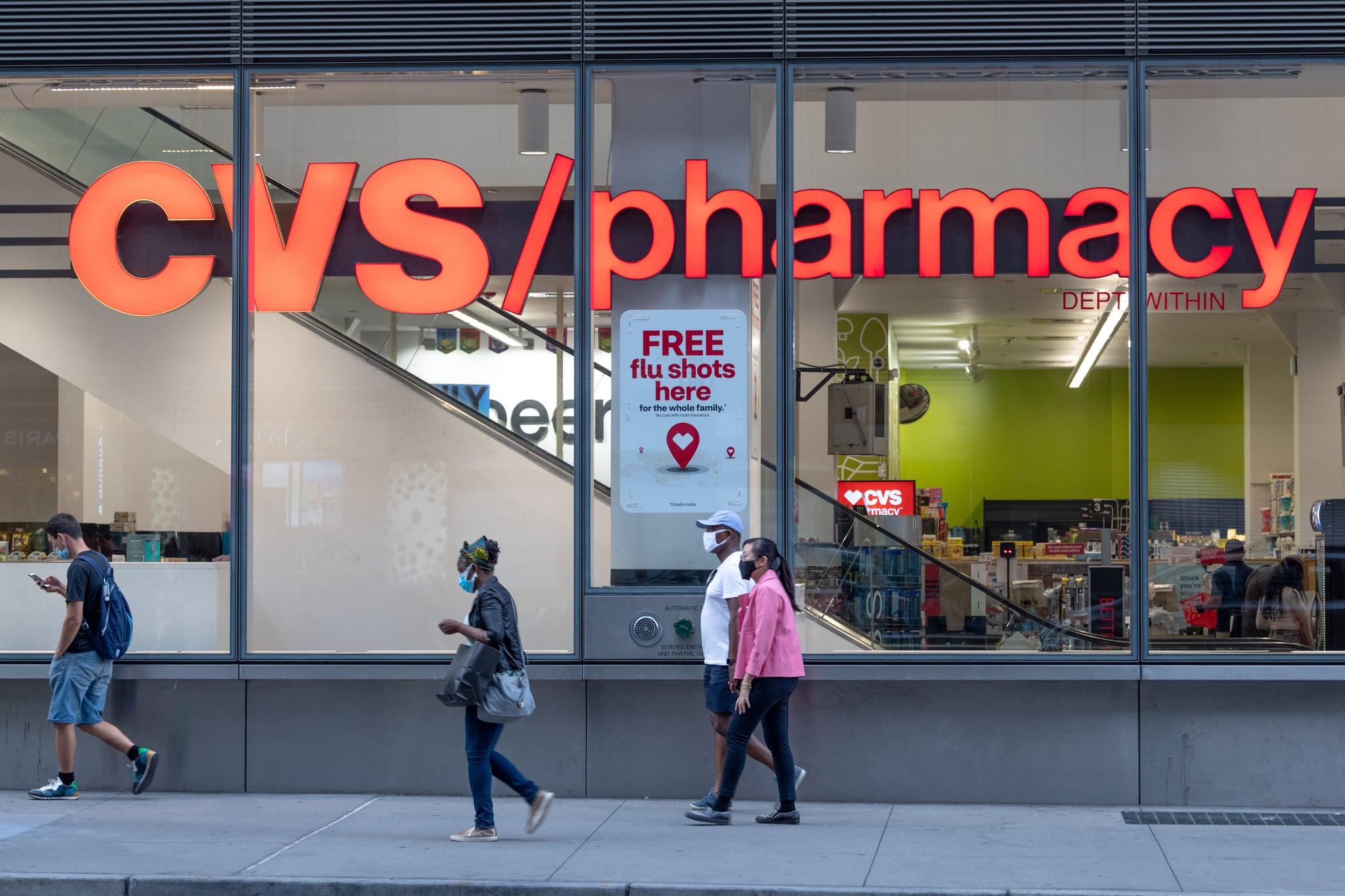 NEW YORK, NEW YORK - AUGUST 26: People wearing masks walks past a CVS Pharmacy where a