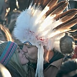 Two protesters in a crowd share a kiss.