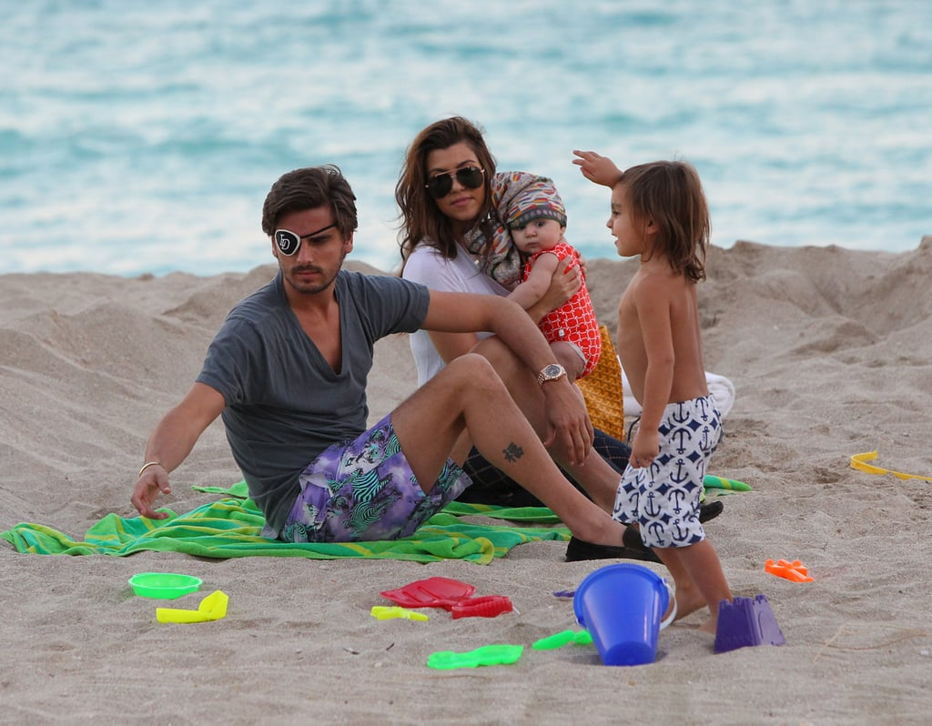 Kourtney Kardashian held her 5-month-old daughter, Penelope, during a trip to the beach in Miami yesterday. They were joined by Kourtney's boyfriend, Scott Disick, and their oldest child, Mason. Kourtney and Scott welcomed Penelope over the Summer and her birth, like Mason's, was featured on their TV show Keeping Up With the Kardashians. Kourtney is currently in the middle of filming the third season of Kourtney and Kim Take Miami, which premieres in January, with her sister Kim Kardashian. The duo went furniture shopping together before Kourtney changed into casual clothes for her afternoon in the sand. They were apart for the Thanksgiving holiday, though, with Kim traveling back to LA and Kourtney staying in Miami with her family of four.