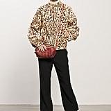 Leopard Goat Hair Bomber ($1,995), Crepe Black Elastic Bottom Pant ($595), Follow Me Black Patent Mid-Calf Boot ($995), Sunset Watersnake Red Cross Body Bag ($625) Photo courtesy of Tamara Mellon
