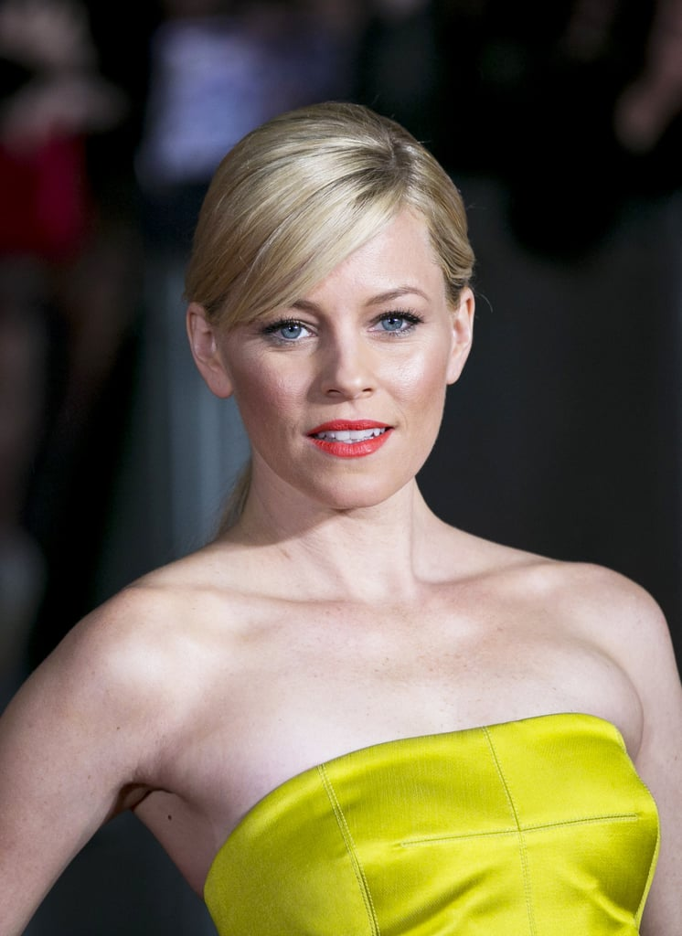 Elizabeth Banks reached for her signature orange lipstick on the red carpet of the Catching Fire world premiere in London.
